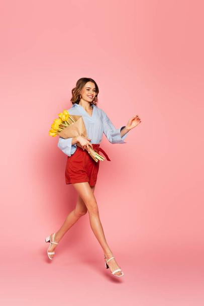 Улыбающаяся женщина с тюльпанами прыгает на розовом фоне  - Фото, изображение