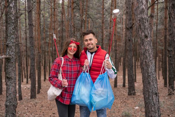 счастливая пара с мешками для мусора  - Фото, изображение