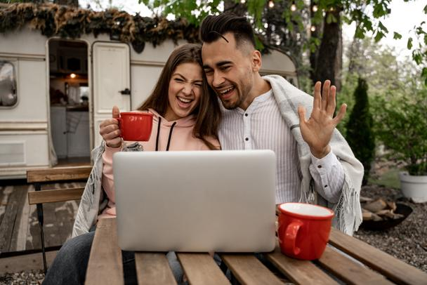 cheerful couple waving hands during video call in camping - Фото, изображение