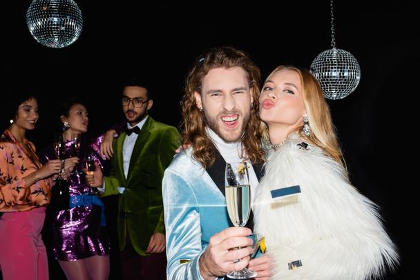 позитивная пара гримасирует на вечеринке с многонациональными друзьями на черном фоне - Фото, изображение