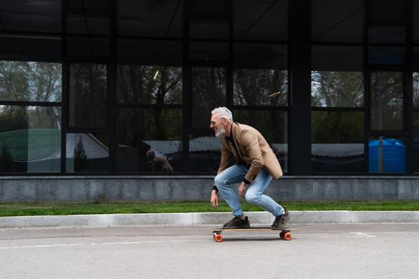 полная длина мужчина средних лет в солнцезащитных очках езда на длинной доске рядом со зданием  - Фото, изображение