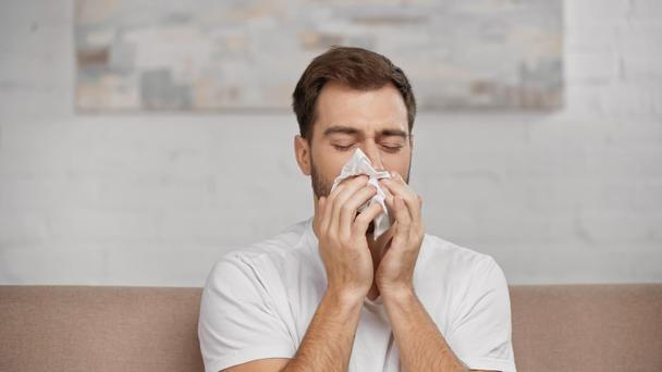 man with pollen allergy sneezing in napkin at home - Фото, изображение