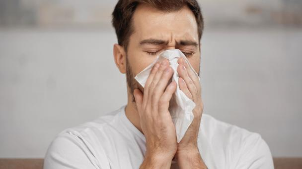 man with allergy sneezing in napkin at home - Фото, изображение