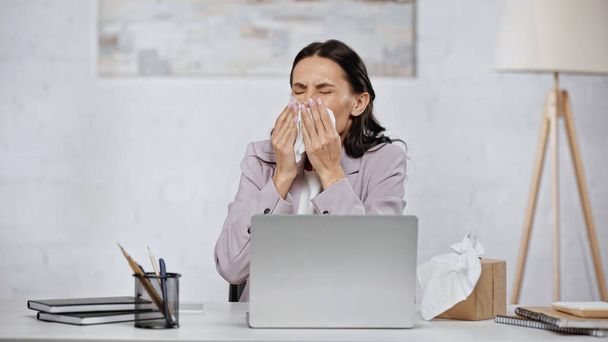 allergic businesswoman sneezing in tissue near laptop on desk - Fotó, kép