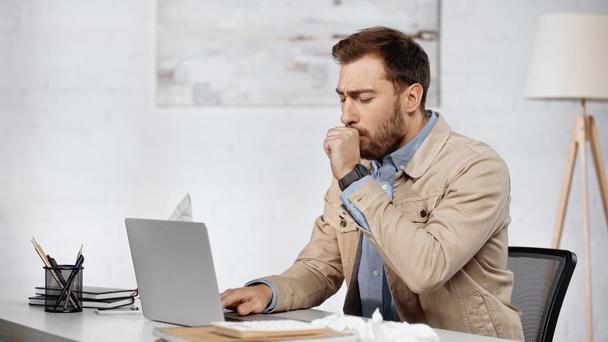allergic businessman couching near laptop on desk  - Фото, изображение