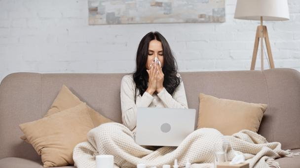ill woman sneezing in tissue while looking at laptop  - Фото, изображение