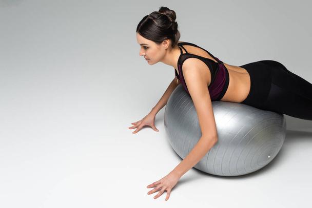 slim sportswoman exercising on fitness ball on grey background - Photo, Image