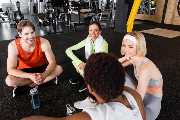 happy multiethnic people sitting on floor and talking in sports center - Photo, Image