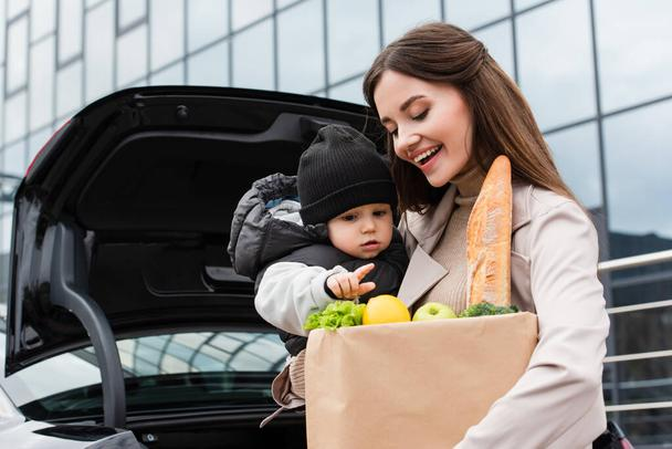 toddler boy pointing at fresh food in shopping bag near happy mother outdoors - Photo, Image