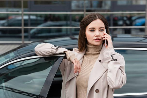 pretty woman in trench coat calling on mobile phone near car - Photo, Image
