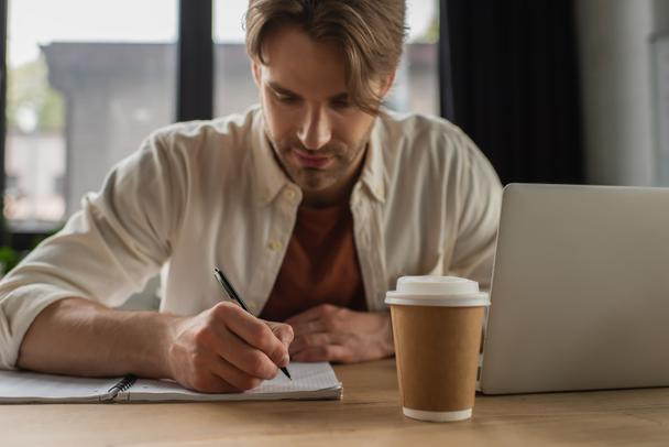 focused young man sitting at desk near paper cup and laptop and writing with pen in notebook in modern office - Photo, Image