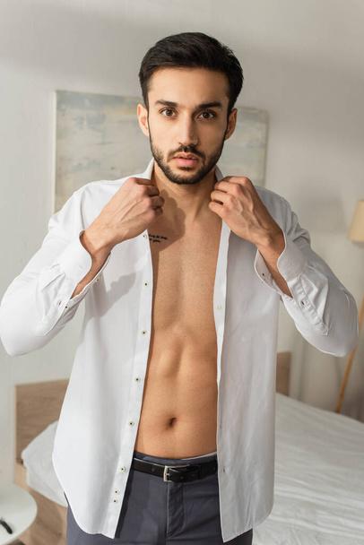 Tattooed man wearing white shirt and looking at camera at home  - Photo, Image