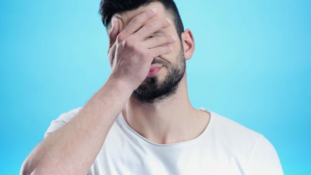 frustrated man obscuring face with hand isolated on blue - Photo, Image