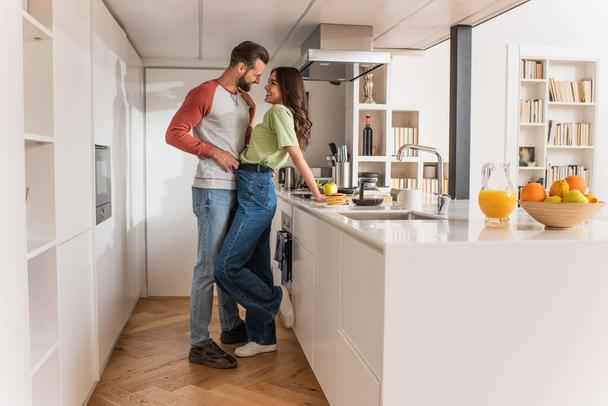 Side view of man hugging smiling girlfriend near breakfast and drinks in kitchen  - Photo, Image