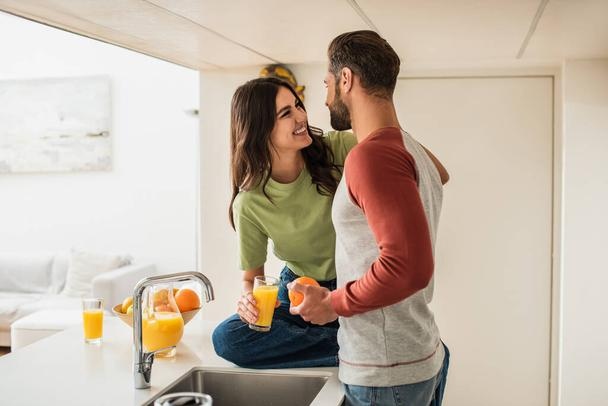 Smiling woman looking at boyfriend with orange near juice in kitchen  - Photo, Image