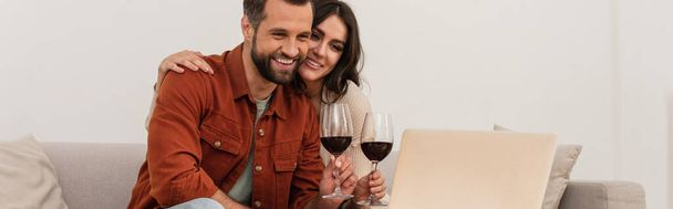 Smiling woman hugging boyfriend with glass of wine near laptop, banner  - Photo, Image