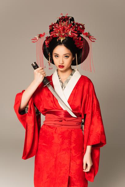 Asian woman holding sword and looking at camera isolated on grey  - Photo, Image
