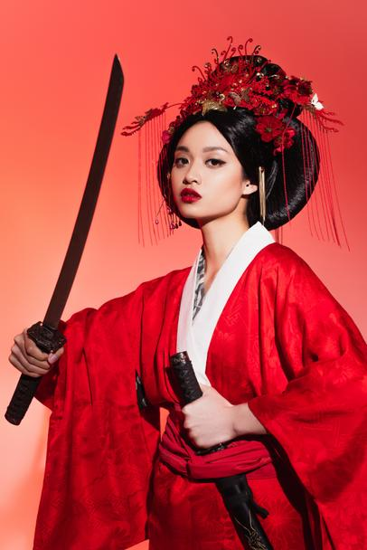 Japanese woman in oriental clothes holding sheath and sword on red background  - Photo, Image