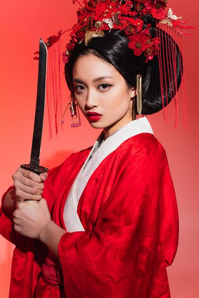 Asian woman in traditional kimono holding sword on red background  - Photo, Image