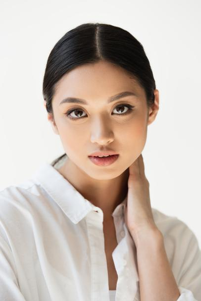 Pretty asian woman in shirt looking at camera isolated on grey - Photo, Image