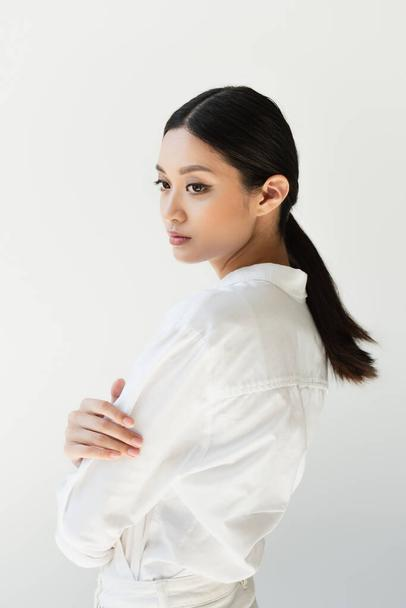 Japanese woman in white clothes looking away isolated on grey - Photo, Image
