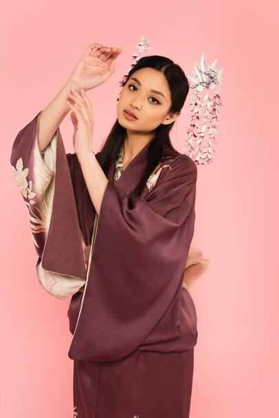 Young asian woman in kimono and hairsticks looking at camera isolated on pink  - Photo, Image