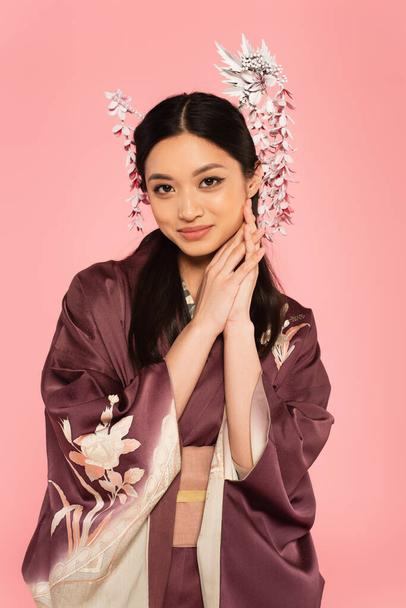 Smiling asian woman with hairsticks in hair looking at camera isolated on pink  - Photo, Image