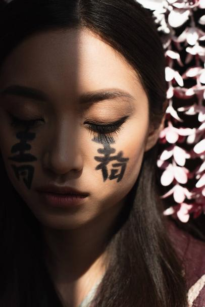 Hieroglyphs on face of young asian woman in light isolated on black  - Photo, Image