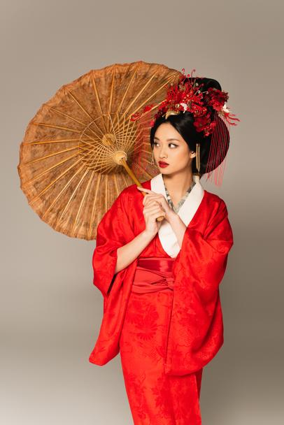 Asian woman in red kimono holding umbrella isolated on grey  - Photo, Image