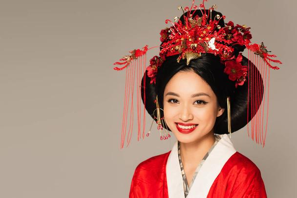 Smiling asian woman with decor in hairdo looking at camera isolated on grey  - Photo, Image