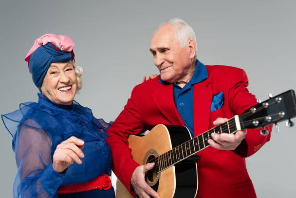 positive elderly man in red blazer playing acoustic guitar near dancing woman in blue dress and turban isolated on grey - Photo, Image