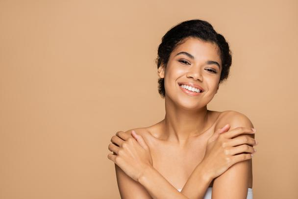 happy african american woman touching bare shoulders and looking at camera isolated on beige  - Photo, Image