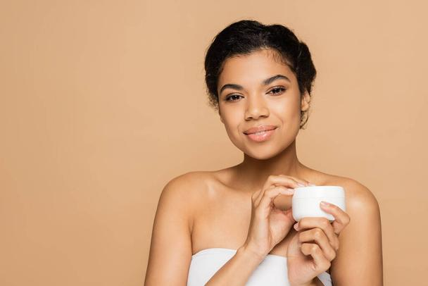 smiling african american woman with bare shoulders holding container with cosmetic cream isolated on beige  - Photo, Image