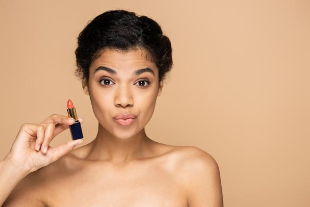 african american woman pouting lips and holding lipstick isolated on beige  - Photo, Image