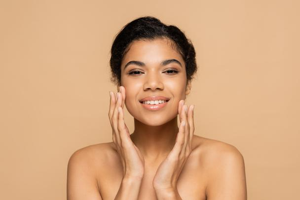 happy african american woman with bare shoulders touching clean face isolated on beige  - Photo, Image