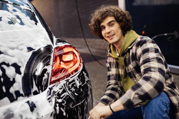 Young man smiling at camera near car in detergent on self service wash - Photo, Image