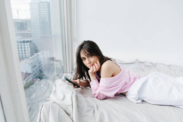 pretty armenian woman looking at camera while lying on white bedding with smartphone - Photo, Image