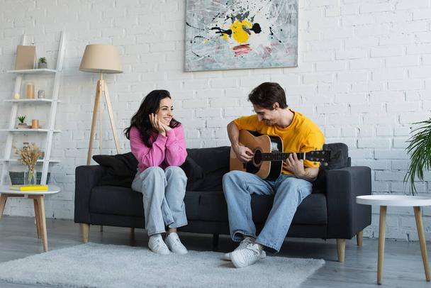 young man playing acoustic guitar near girlfriend with hands near face at home - Photo, Image
