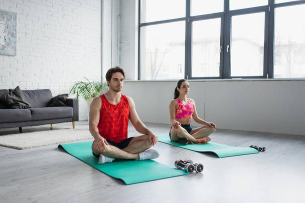 concentrated young couple in sportswear sitting on fitness mats with crossed legs at home - Photo, Image