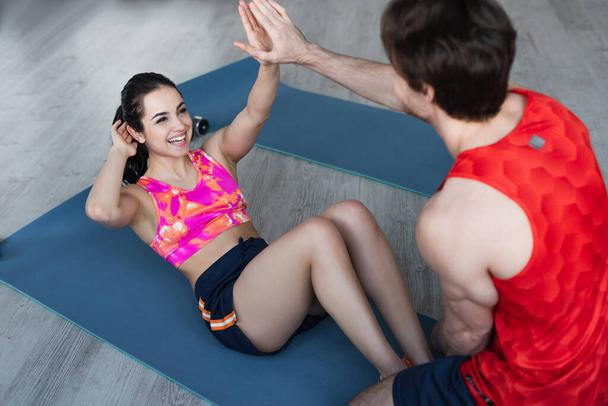 young couple with high five gesture doing sit ups on fitness mat at home - Photo, Image