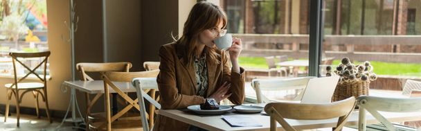 Young stylish woman drinking coffee near dessert in cafe, banner  - Photo, Image