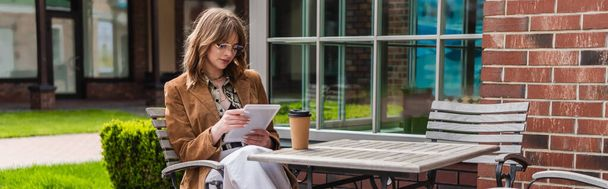 stylish woman in sunglasses and jacket holding digital tablet near paper cup on table, banner - Photo, Image