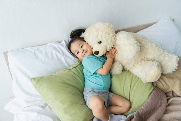 Smiling asian kid holding teddy bear on bed  - Photo, Image