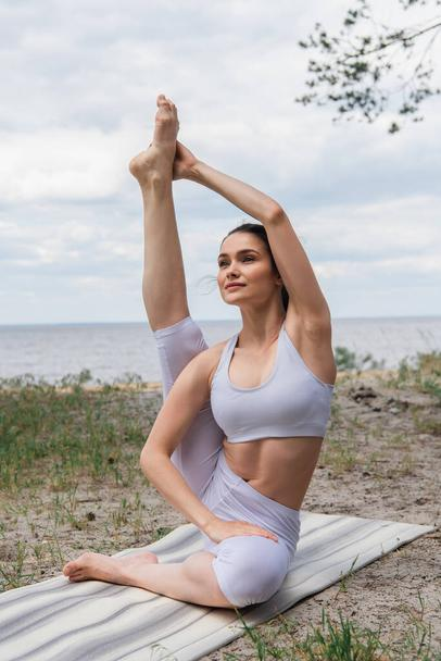 flexible young woman in crop top and leggings stretching on yoga mat near sea - Photo, Image