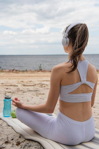back view of young woman in headphones listening music while meditating on yoga mat  - Photo, Image