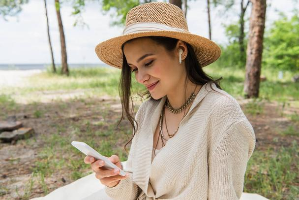 positive young woman in straw hat and wireless earphones using smartphone in forest  - Photo, Image