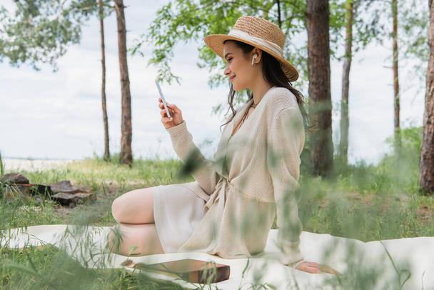 smiling woman in straw hat and wireless earphones using smartphone while sitting on picnic blanket  - Photo, Image