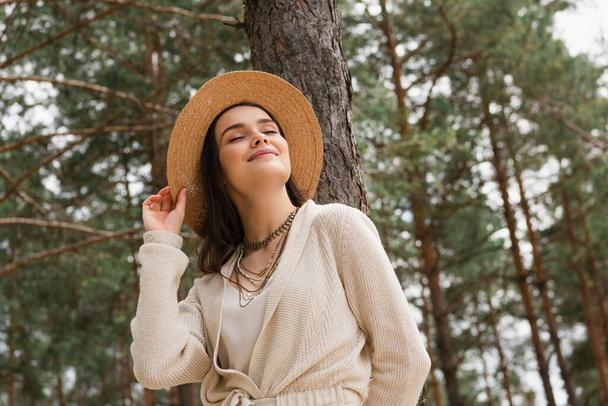 cheerful young woman adjusting straw hat and smiling in woods - Photo, Image