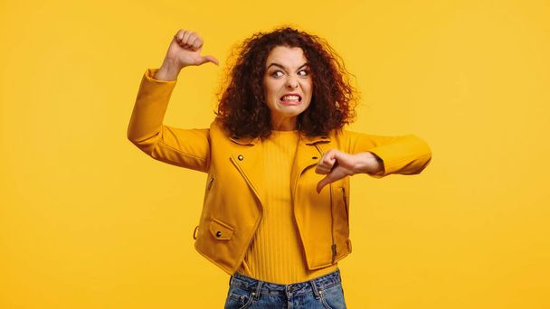 dissatisfied young woman showing thumbs down isolated on yellow - Photo, Image