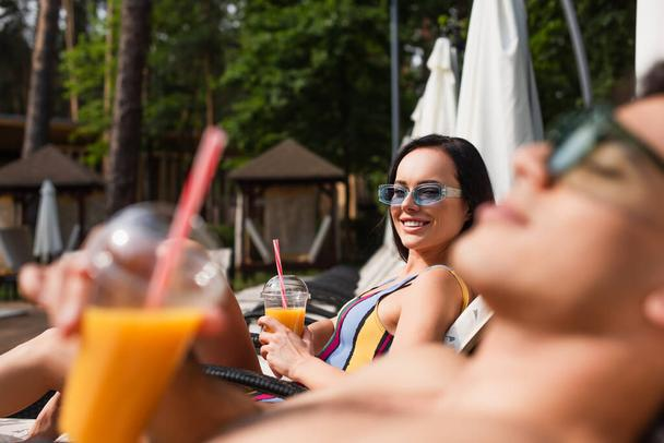 Cheerful woman with drink looking at shirtless boyfriend on blurred foreground outdoors  - Photo, Image